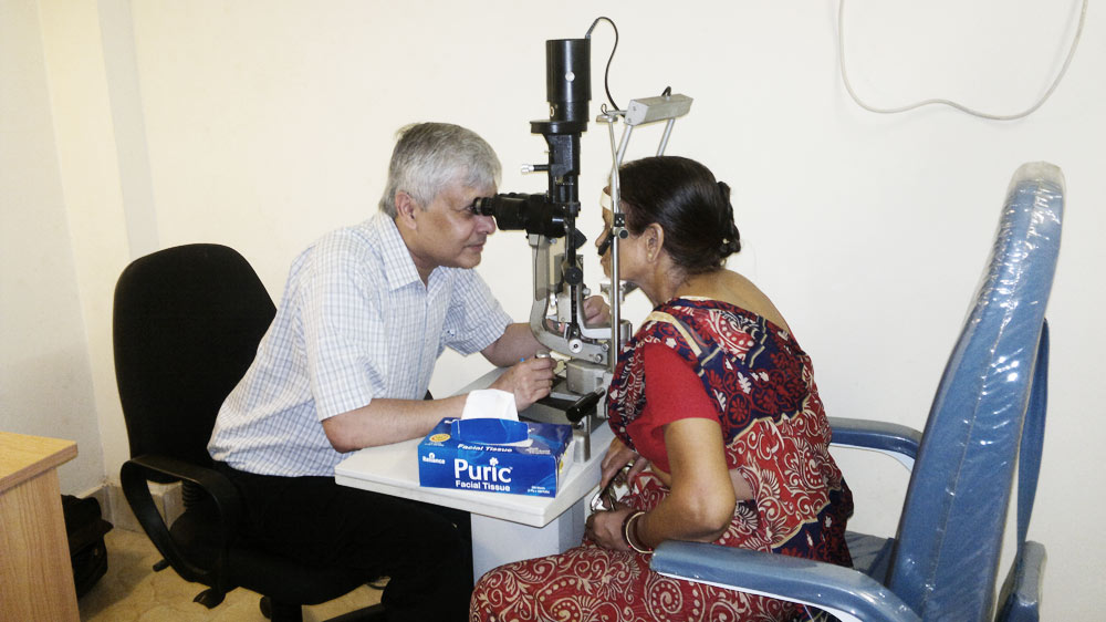 Dr Somdutt Prasad closely examining the eyes of a patient