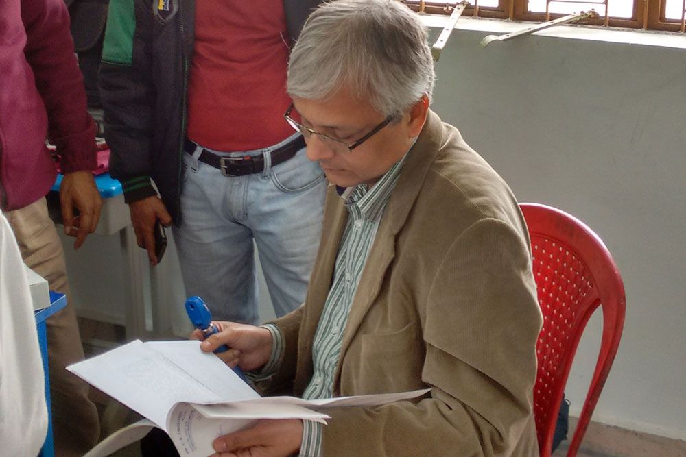 Dr Somdutt Prasad examining case history of a patient during free eye check-up camp