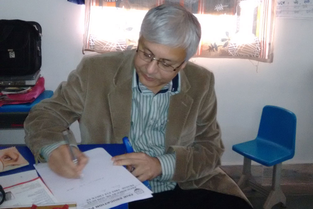 Dr Somdutt Prasad writing a prescription